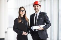 Привлекательное дело человека и женщины объединяется в команду работая конструкция на строительной площадке около панорамных окон Стоковые Фото