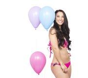 Привлекательное молодое усмехаясь брюнет держа красочные воздушные шары Стоковая Фотография