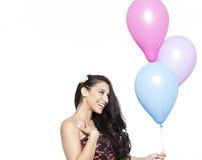 Привлекательное молодое усмехаясь брюнет держа красочные воздушные шары Стоковое фото RF