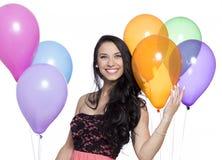 Привлекательное молодое усмехаясь брюнет держа красочные воздушные шары Стоковая Фотография RF