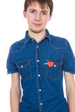 Привлекательное положение мальчика изолированное на белой предпосылке с красным бумажным сердцем в его карманн стоковое фото