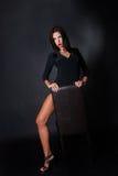 Привлекательное платье черноты носки брюнет сидя на кожаном стуле Стоковые Изображения