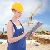 Привлекательное сочинительство построителя женщины что-то в доске сзажимом для бумаги Стоковые Фотографии RF