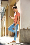 Привлекательное текстовое сообщение мобильного телефона чтения молодого человека Стоковые Фото