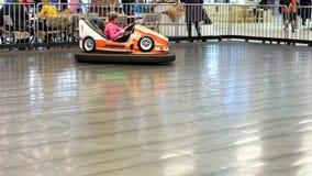 Привлекательность, дети едет на электрической машине в парке атракционов