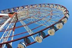 Привлекательность колеса Ferris с красными и голубыми кабинами в парке атракционов ` s детей в городе на голубом Стоковая Фотография