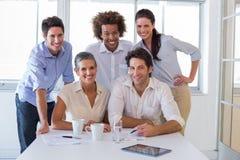 Привлекательные бизнесмены усмехаясь в рабочем месте Стоковая Фотография