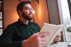 Привлекательные бородатые стекла молодого человека нося сидя в кафе Стоковая Фотография