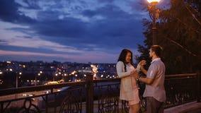 Привлекательные вскользь одетые пары наслаждаются романтичной прогулкой наряду с видом на город Женщина показывать человек для то сток-видео