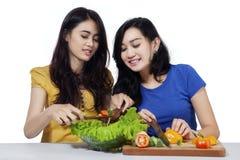 Привлекательные девушки подготавливая салат овощей Стоковое Изображение RF