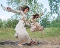 Привлекательные девушки скачут через огонь Стоковые Фото