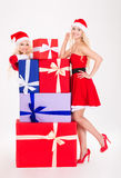 Привлекательные женщины в Санта Клаусе одевают представлять с красочными подарками Стоковое Изображение
