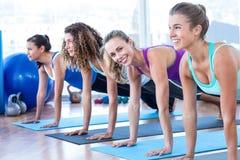 Привлекательные женщины делая представление планки в фитнес-центр Стоковое фото RF