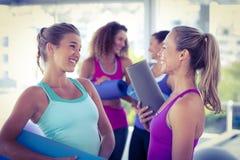 Привлекательные женщины смотря один другого и усмехаясь в студии фитнеса Стоковая Фотография RF