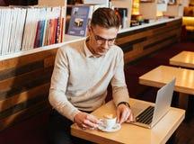 Привлекательные кофе молодого человека выпивая и компьтер-книжка использования Стоковые Изображения