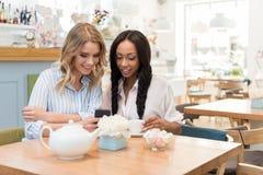 Привлекательные многонациональные женщины используя smartphone пока сидящ на кафе Стоковое Изображение RF