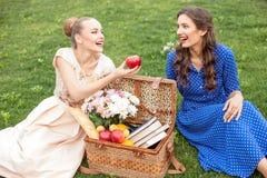 Привлекательные молодые женщины отдыхают в парке Стоковое фото RF
