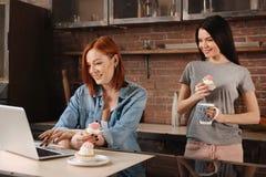 Привлекательные молодые женщины смотря компьтер-книжку Стоковые Фото