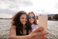 Привлекательные молодые женщины усмехаясь и принимая selfie Стоковое фото RF