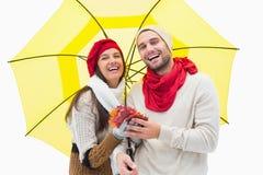 Привлекательные молодые пары в теплых одеждах держа зонтик и листья Стоковое Фото