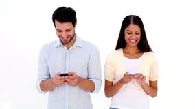 Привлекательные молодые пары отправляя СМС на телефонах