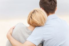 Привлекательные молодые пары сидя на пляже на лете Стоковое Изображение