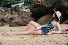 Привлекательные лож девушки загорая на песчаном пляже с драконом приносить в ее руке Стоковые Изображения RF