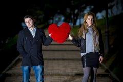 Привлекательные пары воюя над сердцем влюбленности pillow Стоковое Изображение RF