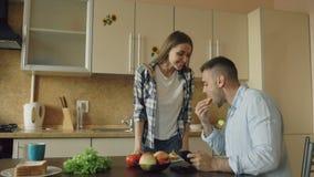 Привлекательные пары в кухне Укомплектуйте личным составом играть видеоигру на таблетке пока его подруга подавая он акции видеоматериалы