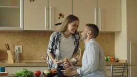 Привлекательные пары в кухне Укомплектуйте личным составом играть занимаясь серфингом планшет пока его подруга подавая он видеоматериал