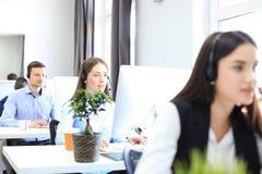 Привлекательные положительные молодые предприниматели и коллеги в офисе центра телефонного обслуживания Стоковое фото RF