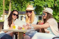 Привлекательные подруги наслаждаясь коктеилями и используя беспроводную связь на цифровой таблетке Стоковое Изображение