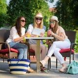 Привлекательные подруги наслаждаясь коктеилями и используя беспроводную связь на цифровой таблетке Стоковая Фотография