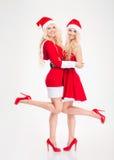 Привлекательные радостные женщины в Санта Клаусе костюмируют положение и усмехаться Стоковое Изображение RF