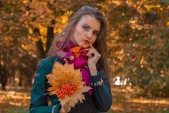 Привлекательные стойки девушки в парке осени держат букет листьев в ее руке и смотреть вперед Стоковая Фотография RF