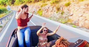 Привлекательные танцы брюнет пока сидящ на рассортированном клобуке автомобиля с откидным верхом, сток-видео