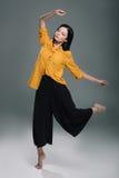 Привлекательные танцы девушки в желтой блузке, изолированной на сером цвете Стоковые Фотографии RF