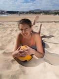 Привлекательные усмехаясь женщины кладя в песок стоковая фотография rf