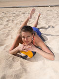 Привлекательные усмехаясь женщины кладя в песок стоковое фото
