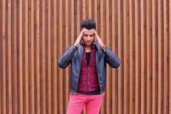 Привлекательный арабский молодой человек, студент чувствует головную боль, с головой a стоковая фотография rf