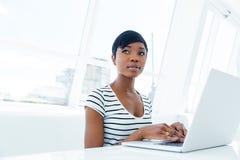 Привлекательный Афро-американский бухгалтер молодой женщины работая в офисе Стоковые Фото