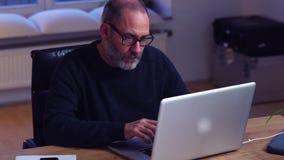 Привлекательный бизнесмен используя портативный компьютер в стильном офисе сток-видео