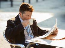 Привлекательный бизнесмен сидя outdoors имеющ кофейную чашку для завтрака рано утром читая новости газеты смотря ослабленный Стоковая Фотография RF