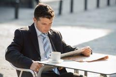 Привлекательный бизнесмен сидя outdoors имеющ кофейную чашку для завтрака рано утром читая новости газеты смотря ослабленный Стоковое Изображение RF