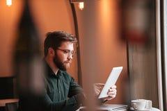 Привлекательный бородатый молодой человек используя планшет Стоковые Фото