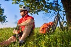 Привлекательный велосипедист сидя на траве около велосипеда и около дерева Стоковые Фото