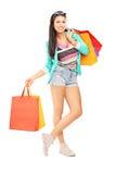 Привлекательный вскользь женский представлять с много хозяйственных сумок Стоковая Фотография