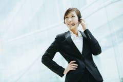 Привлекательный женский азиатский носить коммерсантки наушники с микрофоном Стоковое Фото