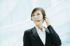 Привлекательный женский азиатский носить коммерсантки наушники с микрофоном Стоковые Фото