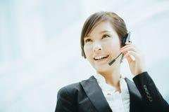 Привлекательный женский азиатский носить коммерсантки наушники с микрофоном Стоковая Фотография RF